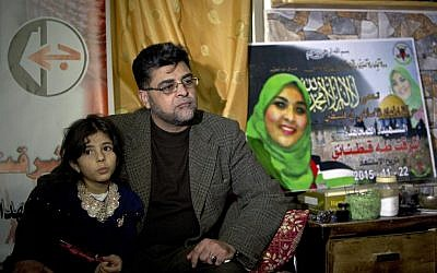 In this Dec. 28, 2015 photo, Taha Qatanani, 44, and his daughter Ranci, 7, sit near a makeshift shrine to honor their daughter and sister, Ashraqat, featuring her image against a backdrop of the Al-Aqsa mosque compound in Jerusalem, in the West Bank city of Nablus. (AP Photo/Majdi Mohammed)