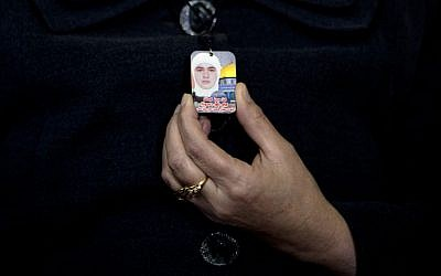 In this Monday, Dec. 28, 2015 photo, Hanan Hassoneh, 45, holds a photo of her daughter Maram, in the West Bank city of Nablus. Maram, a top English student at An-Najah University and a devout Muslim, was shot and killed when she tried to stab Israeli soldiers at a West Bank checkpoint on Dec. 1, 2015. (AP Photo/Majdi Mohammed)
