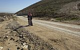 A Palestinian walks on a newly-made section of a road that was financed by the European Union, on the outskirts of the West Bank village of Taqoa, near Bethlehem, January. 16, 2016. (AP Photo/Nasser Nasser)