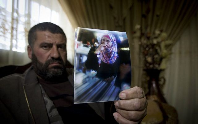 In this Dec. 28, 2015 photo, Ramiz Hassoneh holds a photo of his daughter, Maram, in the West Bank city of Nablus. (AP Photo/Majdi Mohammed)