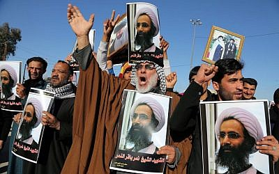 Iraqi Shiite protesters chant slogans against the Saudi government as they hold posters showing executed Sheikh Nimr al-Nimr, Najaf, January. 4, 2016. (AP/Karim Kadim, File)
