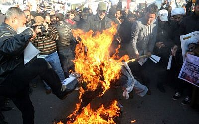 In this Monday, Jan. 4, 2016 file photo, followers of Shiite cleric Muqtada al-Sadr burn an effigy of King Salman of Saudi Arabia as they hold posters of Sheikh Nimr al-Nimr during a demonstration in Baghdad, Iraq. (AP Photo/Khalid Mohammed, File)