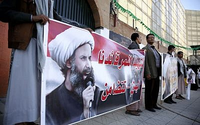 Houthi Shiite rebels hold posters of late cleric Nimr al-Nimr, who was executed in Saudi Arabia, during an anti-Saudi protest outside the Saudi embassy in Sanaa, Yemen, Thursday, January 7, 2016. (AP Photo/Hani Mohammed)