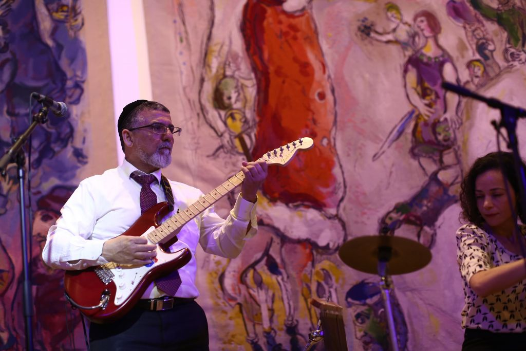 Shas MK Yitzhak Vaknin shreds on the electric guitar at the Knesset in Jerusalem on Tuesday, January 19 2016. (Knesset)