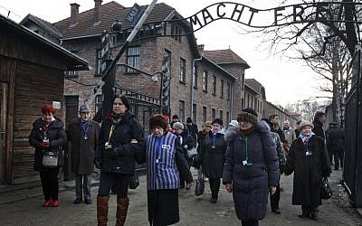 Holocaust survivors walk with others through the main gate of the former Nazi death camp Auschwitz in Poland, on January 27, 2016 (AP/Czarek Sokolowski)