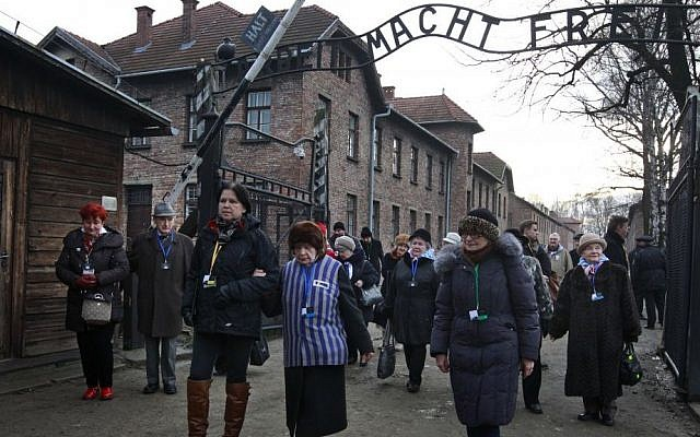 File: Holocaust survivors walks with others through the main gate of the former Auschwitz Nazi death camp in Oswiecim, Poland on Jan. 27, 2016, the 71st anniversary of the death camp's liberation by the Soviet Red Army in 1945. (AP Photo/Czarek Sokolowski)