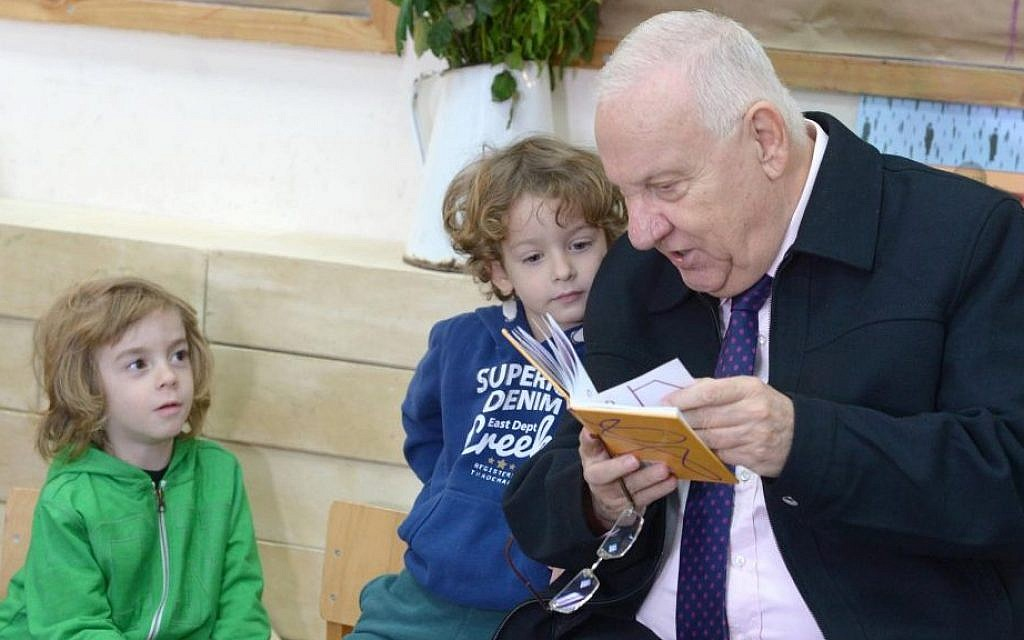 President Reuven Rivlin reading a book to the children at Hadas Kindergarten, on Sunday, January 3 2016. (Mark Neyman/GPO)