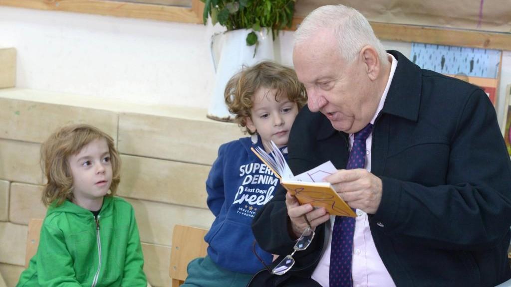 President Reuven Rivlin reading a book to the children at Hadas Kindergarten, on Sunday, January 3 2016. (Mark Neyman/GPO)