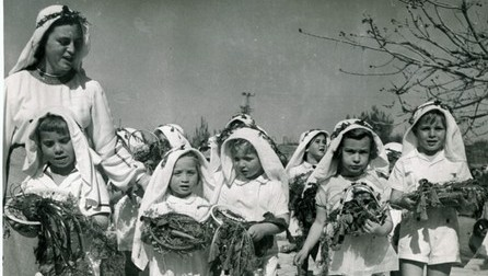 "Children in 1953 bring ""bikkurim,"" representations of the harvest of the past year, on Tu BShvat. (JNF-KKL Archive photo)"