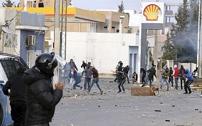 Protesters throw items to police forces in the city of Ennour, near Kasserine, Tunisia, Wednesday, Jan. 20, 2016. (AP Photo/Moncef Tajouri)