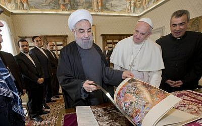 Iranian President Hassan Rouhani leafs through a book he gave to Pope Francis as a gift, during their private audience at the Vatican,Tuesday, Jan. 26, 2016. (AP Photo/Andrew Medichini, Pool)