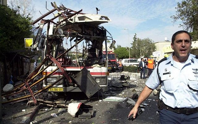 An Israeli police officer at the scene of a public bus bombing in the northern Israeli city of Haifa, Wednesday, March 5, 2003. A Palestinian suicide bomber blew himself up aboard the crowded bus, killing at least 17 people and injuring dozens. (Ronen Lidor/ Flash90)
