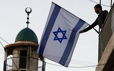 A Jewish-Israeli raising the Israeli flag near the Old City of Jerusalem, which has seen an influx of Jewish residents in predominantly Arab areas. (Abir Sultan/Flash 90)