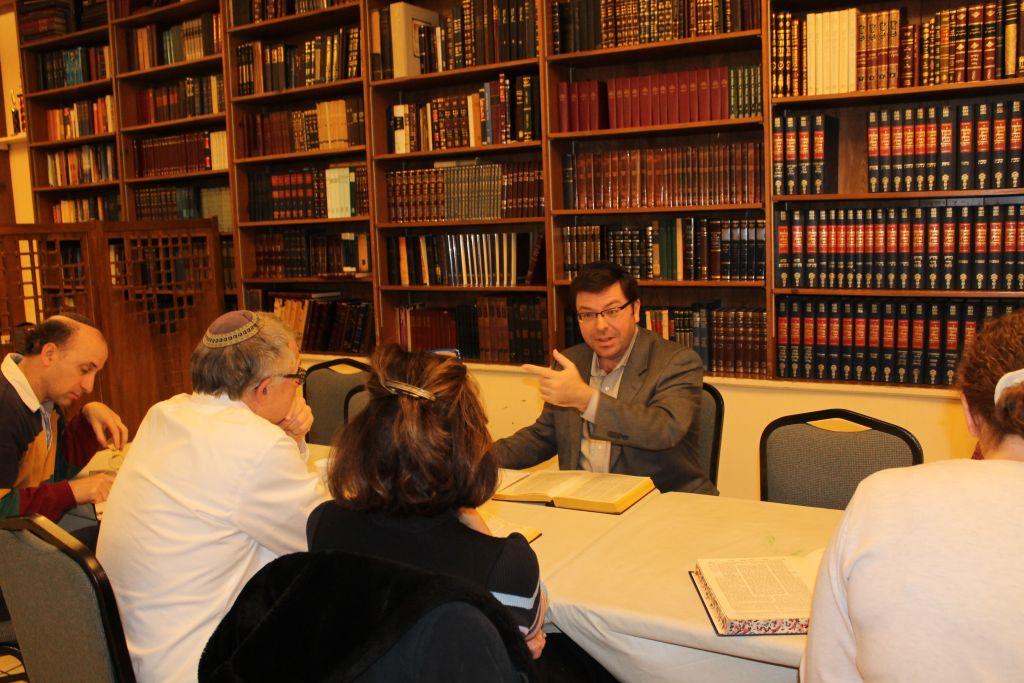 Rabbi Avidan Milevsky, gesturing, leading a Sunday morning Talmud class after services at Kesher Israel in Washington, D.C., December 20, 2015. (Uriel Heilman/JTA)