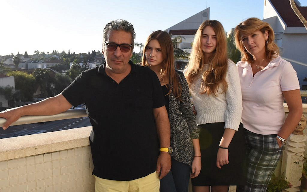 Catherine Berdah, right, with her husband and daughters in their apartment in Ra'anana, Israel. (Cnaan Liphshiz/JTA)