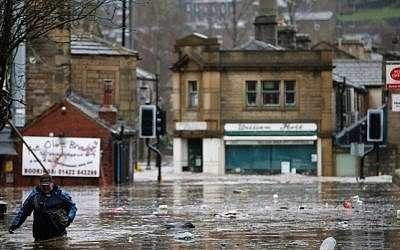 A man wades through flood waters at Hebden Bridge in West Yorkshire, England. (Peter Byrne/PA via AP)