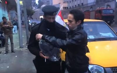 Egyptian actor and prankster Shady Hussein hands a policeman an inflated condom on January 25, 2016. (YouTube)