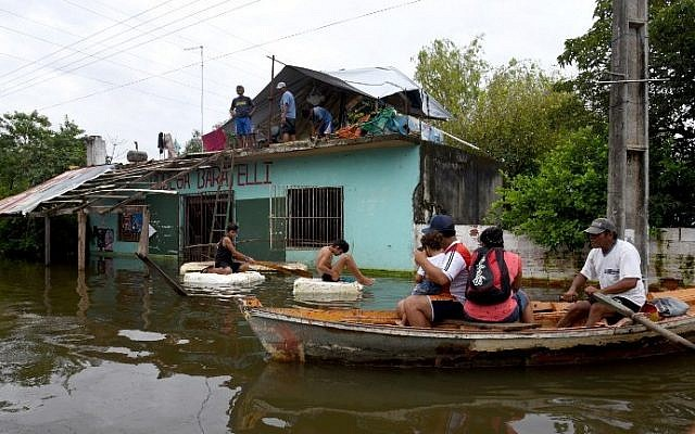 Local residents navigate along a flooded street in Asuncion, on January 4, 2016. So far, six people have died, more than 100,000 people have been displaced, 25,766 families are in shelters, 125,000 homes are without electric power. (AFP PHOTO/NORBERTO DUARTE)