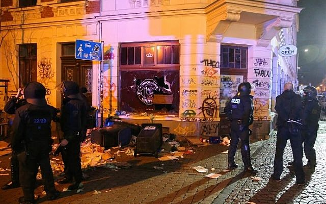 Police officers in riot gear stand in front of a damaged building in a street of the Connewitz district in Leipzig on January 11, 2016 where far-right supporters and hooligans went on a rampage on the sidelines of a xenophobic rally in Leipzig, setting cars on fire and smashing windows. (AFP/ dpa/Jan Woitas)