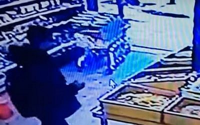 Security footage shows a suspected Arab Israeli gunman in a grocery on Dizengoff Street in Tel Aviv, seconds before he stepped outside and opened fire with a machine gun, killing two people, on January 1, 2016.  (screen capture)