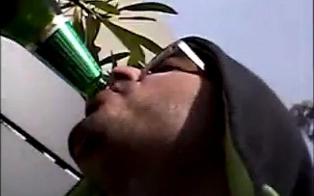 A still image of Tel Aviv gunman Nashat Milhem drinking beer taken from a series of undated videos released January 27, 2016 by the Shin Bet security service. (screen capture)