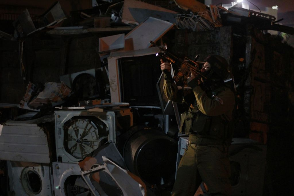 A soldier provides cover to the team that entered the home of a suspect in the Palestinian city of Qalqilya on January 14, 2016. The family's yard was filled with stacks of used appliances, including a five-foot high, 20-foot long wall of air conditioners, not seen. (Judah Ari Gross/Times of Israel)