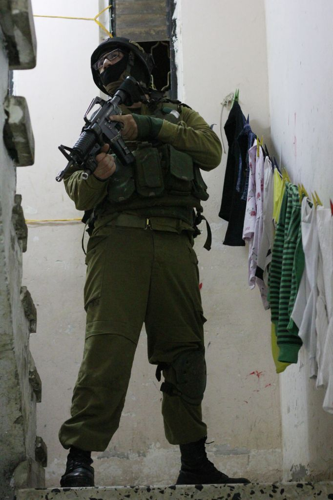 A soldier stands guard in the stairwell as the other members of his unit enter the home of a Palestinian teenager suspected of having thrown rocks at IDF troops in Qalqilya, on January 14, 2016. The suspect was only 14 years old. Due to his young age, it was not clear how the IDF would proceed -- if he would be arrested or merely given a warning. (Judah Ari Gross/Times of Israel)
