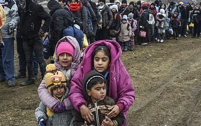 Children pose as they wait with other migrants and refugees in line for a security check after crossing the Macedonian border into Serbia, near the village of Miratovac, on January 26, 2016. (AFP / ARMEND NIMANI)