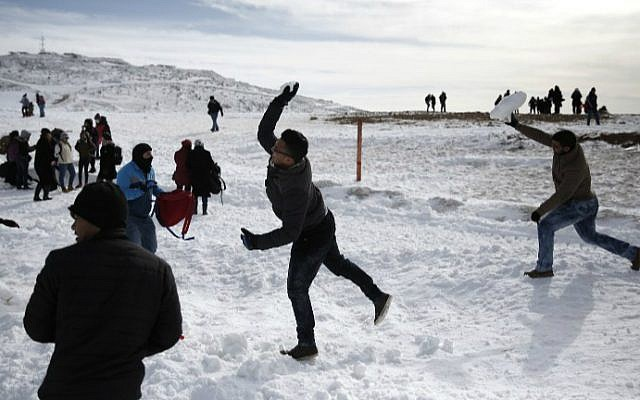 Arab boys throw snowballs at their friends at the Mount Hermon ski resort on the Golan Heights, on January 21, 2016. (Thomas Coex/AFP)