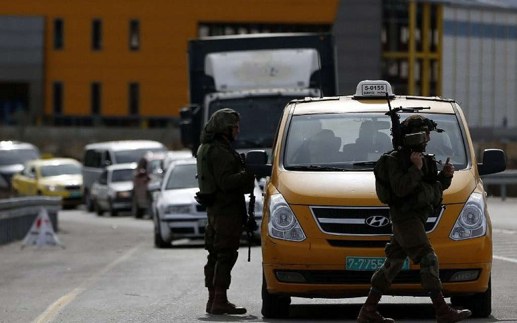 File: An Israeli soldier checks the documents of the Palestinian passengers of a taxi on their way out of Ramallah on February 1, 2016. (AFP/Abbas Momani)