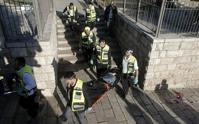 Medics carry the bodies of two Palestinian attackers killed during a shooting and stabbing assault at Damascus Gate, one of the gates of Jerusalem's Old City, February 3, 2016. (AFP/Ahmad Gharabli)