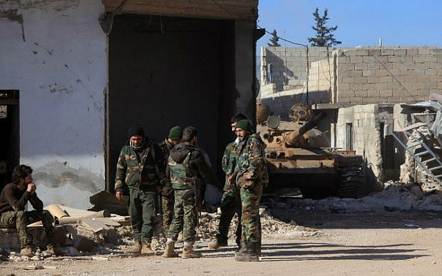 Syrian government forces stand in the village of Tal Jabin, north of the embattled city of Aleppo, as they advanced to break a three-year rebel siege of two government-held Shiite villages, Nubol and Zahraa, and take control of parts of the supply route to the area on February 3, 2016. (George Ourfalian/AFP)