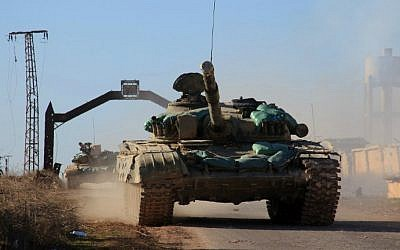 Syrian government tanks drive in the village of Tal Jabin, north of the embattled city of Aleppo, as they advanced to break a three-year rebel siege of two government-held Shiite villages, Nubol and Zahraa, and take control of parts of the supply route to the area on February 3, 2016. (George Ourfalian/AFP)