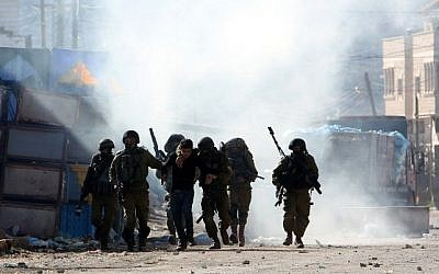 Israeli security forces arrest a Palestinian man during clashes in Qabatiya, near Jenin in the north of the West Bank, on February 4, 2016 (Jaafar Ashtiyeh/AFP)