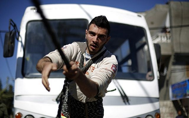 Palestinian Mohammed Baraka, who has become something of a local hero for his strength, pulls a bus tied to a rope as he performs a trick in Deir el-Balah, in central Gaza, on January 4, 2016. (AFP/Mohammed Abed)