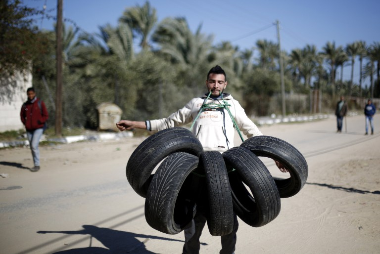 Palestinian Mohammed Baraka, who has become something of a local hero for his strength, has concrete bricks broken on his back as he performs a trick in Deir Al-Balah, in central Gaza, on January 4, 2016. (AFP / MOHAMMED ABED)