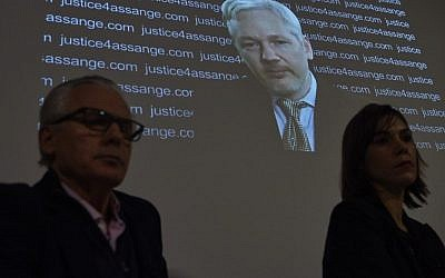 WikiLeaks founder Julian Assange is projected onto a screen behind Spanish jurist Baltasar Garzon (L) and Australian lawyer Melinda Taylor (R) as he speaks via video-link from the Ecuadorian embassy at a press conference at the Frontline Club in central London on February 5, 2016. (AFP / NIKLAS HALLE'N)