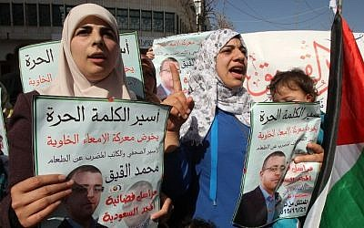 Faihaa al-Qiq, left, the wife of hunger-striking Palestinian prisoner Mohammed al-Qiq, demonstrates with fellow supporters in solidarity with him after Friday prayers in the West Bank town of Hebron on February 5, 2016. (AFP/HAZEM BADER)