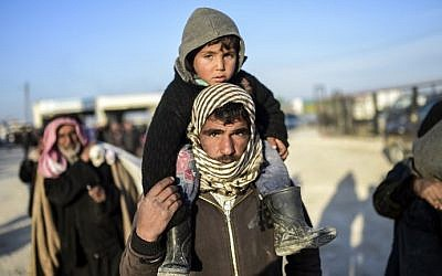 A man carries a child on his shoulders as Syrians fleeing the northern embattled city of Aleppo wait on February 5, 2016 in northern Syria, near the Turkish border. (AFP / BULENT KILIC)