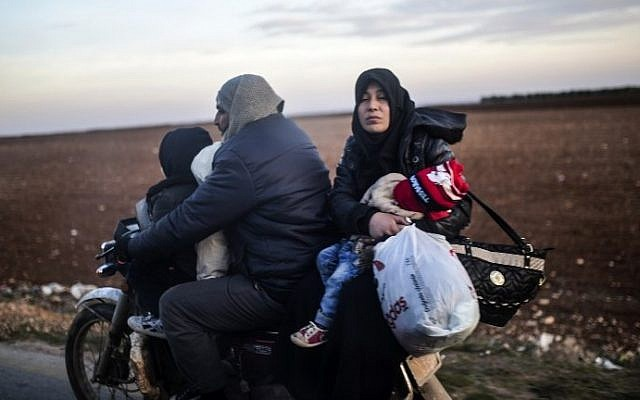 A Syrian family fleeing the northern embattled city of Aleppo wait on February 5, 2016 in Bab-Al Salama, next to the city of Azaz, northern Syria, near Turkish crossing gate. (AFP / BULENT KILIC)