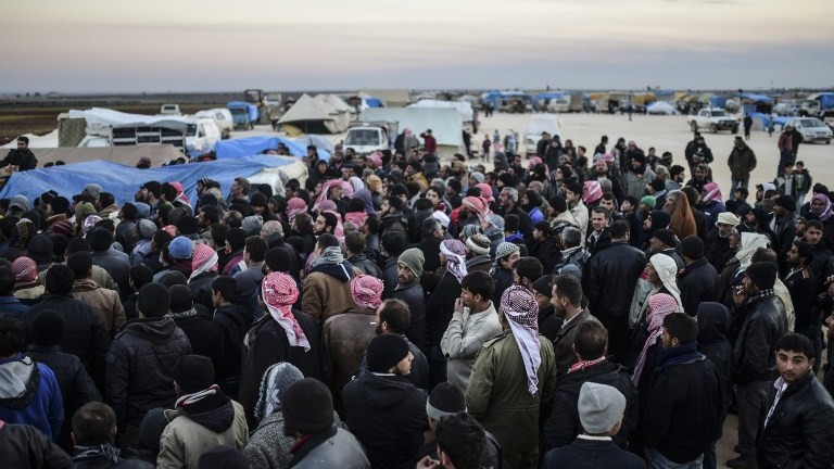 Syrians fleeing the northern embattled city of Aleppo wait on February 5, 2016 in Bab-Al Salama, next to the city of Azaz, northern Syria, near Turkish crossing gate. (AFP / BULENT KILIC)