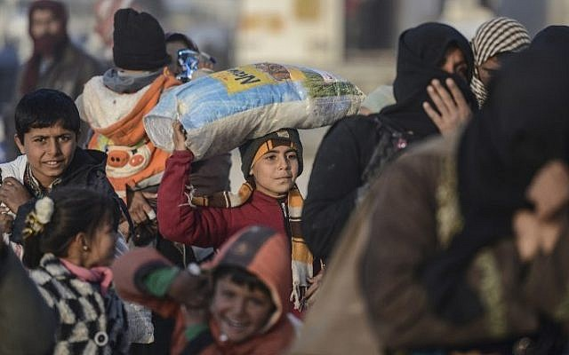 Children carry bags as Syrians fleeing the northern embattled city of Aleppo wait on February 5, 2016 in Bab-Al Salama, next to the city of Azaz, northern Syria, near Turkish crossing gate. (AFP / BULENT KILIC)
