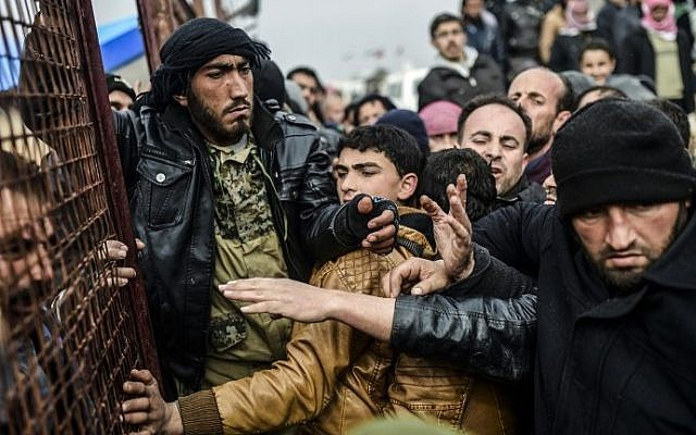 Refugees push each other as they wait for tents as Syrians fleeing the northern embattled city of Aleppo wait on February 6, 2016 in Bab al-Salama, near the city of Azaz, northern Syria, near the Turkish border crossing. (Bulent Kilic/AFP)