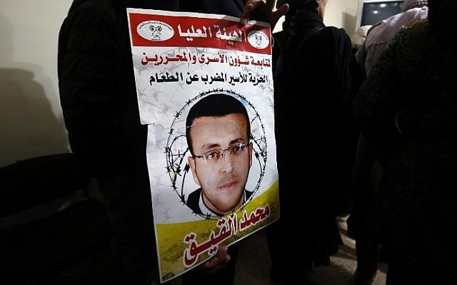 A supporter of hunger striking Palestinian prisoner Mohammed al-Qiq holds a portrait as he demonstrates in solidarity with him on February 7, 2016, outside the International Committee of the Red Cross (ICRC) offices in the West Bank city of Ramallah. (AFP / ABBAS MOMANI)