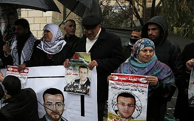 Supporters of hunger-striking Palestinian prisoner Mohammed al-Qiq hold portraits as they demonstrate in solidarity with him outside the offices of the International Committee of the Red Cross near the West Bank city of Ramallah, February 7, 2016. (AFP/Abbas Momani)
