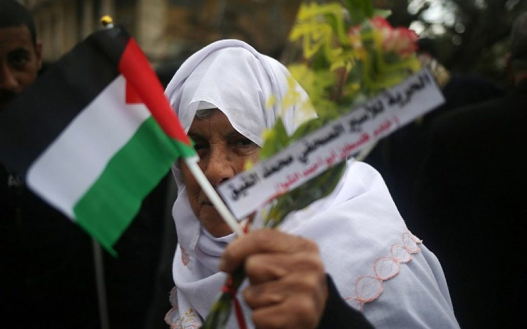 A Palestinian woman holds flowers and her national flag during a demonstration in support of hunger striking Palestinian journalist Mohammed al-Qiq, on February 8, 2016, in Gaza City. (AFP / MOHAMMED ABED)