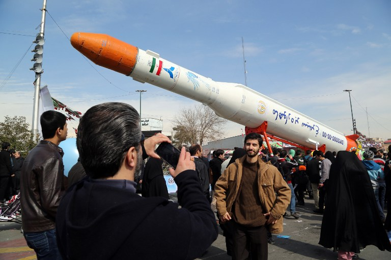 Iranians take photos of the Simorgh satellite rocket during celebrations to mark the 37th anniversary of the Islamic Revolution, in Tehran, February 11, 2016. (AFP/Atta Kenare)