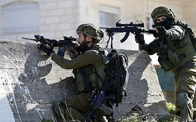 Illustration. Israeli soldiers aim their weapons at Palestinian protesters on February 15, 2016 at the Amari Palestinian refugee camp, near the West Bank city of Ramallah, during clashes.  (AFP/ABBAS MOMANI)