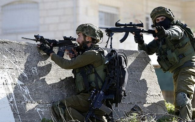 Illustrative: Israeli soldiers aim their weapons at Palestinian protesters on February 15, 2016 at the Amari Palestinian refugee camp, near the West Bank city of Ramallah, during clashes.  (AFP/ABBAS MOMANI)