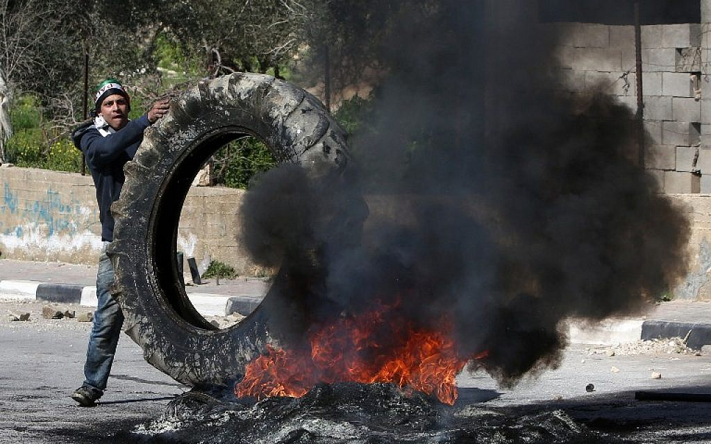 A Palestinian demonstrator places a tire onto a fire during clashes with Israeli borderguards in the village of Araka on February 15, 2016. (AFP/JAAFAR ASHTIYEH)